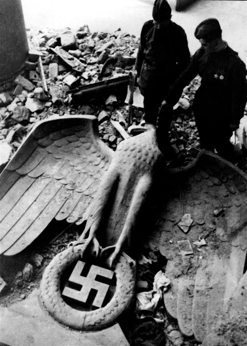 Miembros del ejército soviético contemplan una estatua caída de un águila imperial con una esvástica tras su victoria en Berlín
